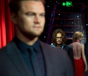 Johnny Depp staring moodily behind Leonardo DiCaprio